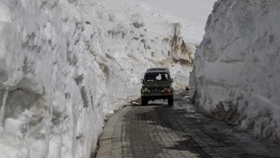An army vehicle drives past walls of snow on the Zojila Pass, about 110 kilometers (68 miles) north of Srinagar,  on April 30, 2016.