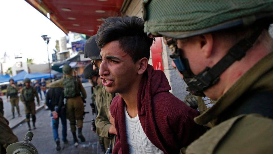Israelis arrest a Palestinian stone thrower during clashes in the city centre of the West Bank town of Hebron on December 10, 2017.
