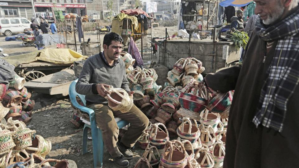 A Kashmiri man inspects a Kangri before purchasing it in Srinagar. These portable pots are considered an enduring symbol of local craft and widely associated as a cost-effective means of battling the region's biting winters.  (Waseem Andrabi / HT Photo)