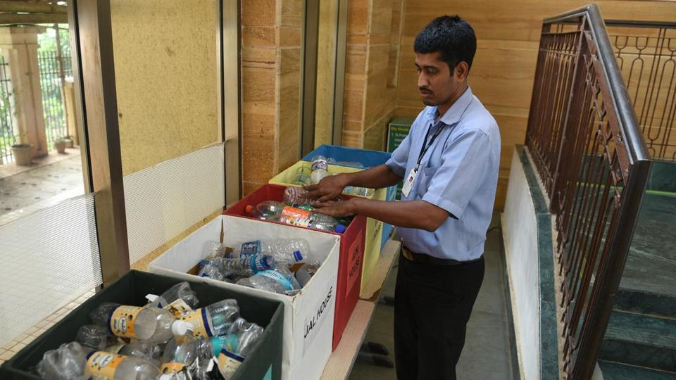 A students adds a plastic bottle to the collection box. The bottles are later sent for recycling.