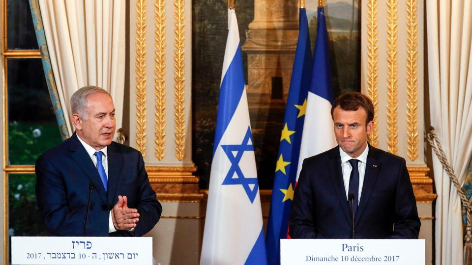 Israeli Prime Minister Benjamin Netanyahu (L) speaks as French President Emmanuel Macron looks on during a joint news conference following their meeting at the Elysee Palace in Paris on December 10, 2017. French President Emmanuel Macron urged Israeli Prime Minister Benjamin Netanyahu to freeze Israeli settlement building during their talks in Paris on December 10.