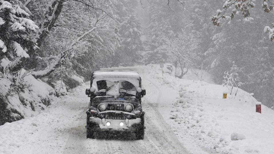 A vehicle drives past a snow-covered Gulmarg-Tangmarg road, about 38 kilometers from Srinagar, on Monday. (waseem andrabi/ht)