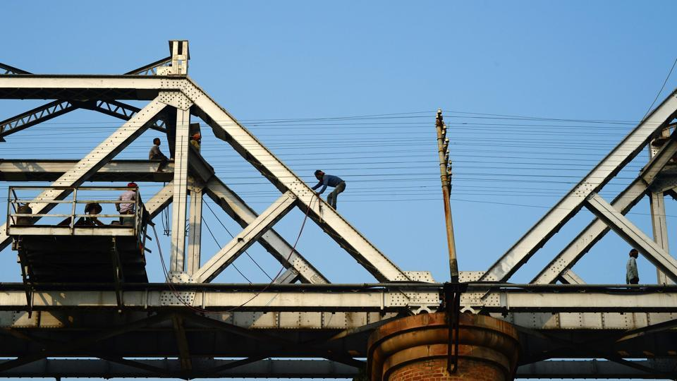 Labourers repair a railway bridge built over the Ganga river in Allahabad on December 7, 2017.