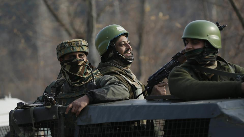Army soldiers share a lighter moment as they guard during a gunbattle at Pakharpore village, south of Srinagar, Kashmir, on Nov. 30, 2017.
