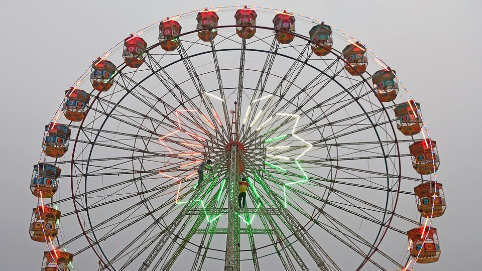Men repair tubelights on a ferris wheel. The 'Urs' festival is an annual celebration in the memory of Hazrat Makhdum Ali Mahimi, a 14th century Sufi scholar.  (Shashi S Kashyap/HT PHOTO)