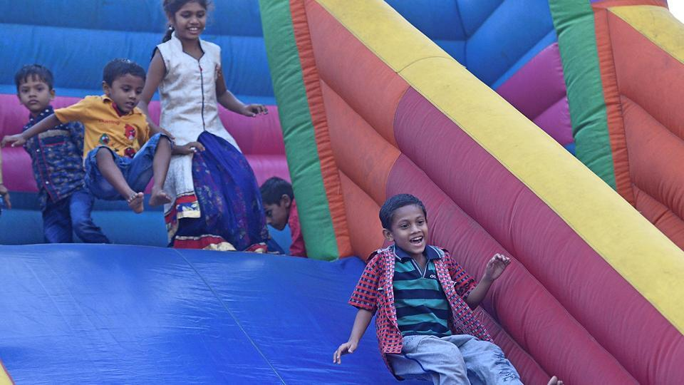 Children slide down an inflatable rainbow slide. (Shashi S Kashyap/HT PHOTO)
