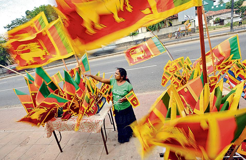 A vendor sells Sri Lankan national flags at a roadside stall in Colombo.