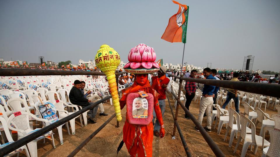 A supporter carries overhead a model of lotus, the election symbol of India's ruling Bharatiya Janata Party.