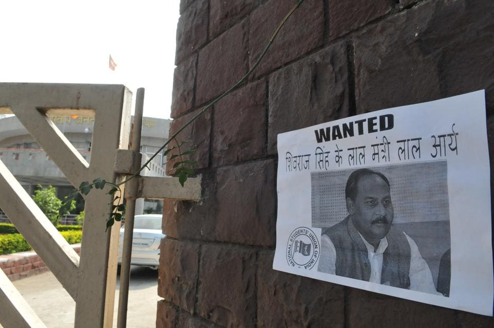 NSUI workers pasted a poster of minister of state for general administration Lal Singh Arya at the gate of state BJP office in Bhopal