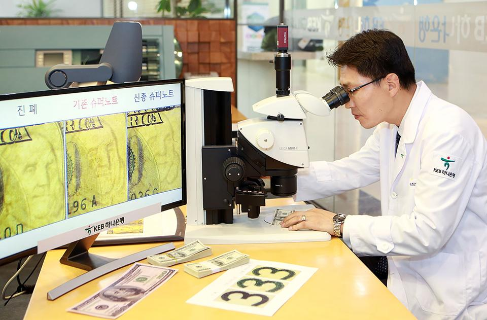 In this handout photo provided by South Korea's KEB Hana Bank, Yi Ho-Joong, who heads the bank's anti-counterfeit centre, inspects a fake $100 'supernote' -- a forgery so fine that it is hard to detect.