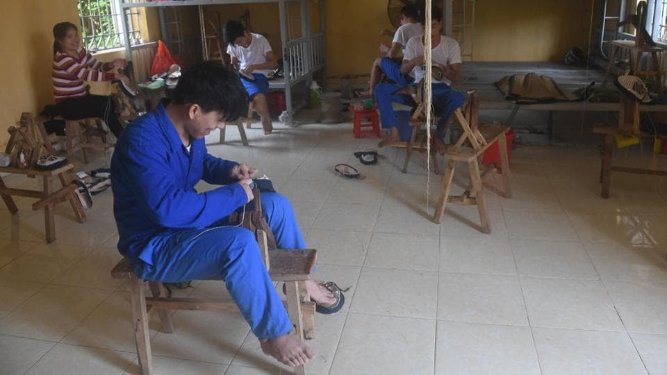 Inmates sew shoes at a drug rehabilitation centre. Most inmates stay for one or two years, or up to four if they are deemed unfit for release, and are subject to a range of daily labour -- from farming cashews to making sportswear for Western clothing brands, which they can sometimes earn a meagre salary from. (AFP)