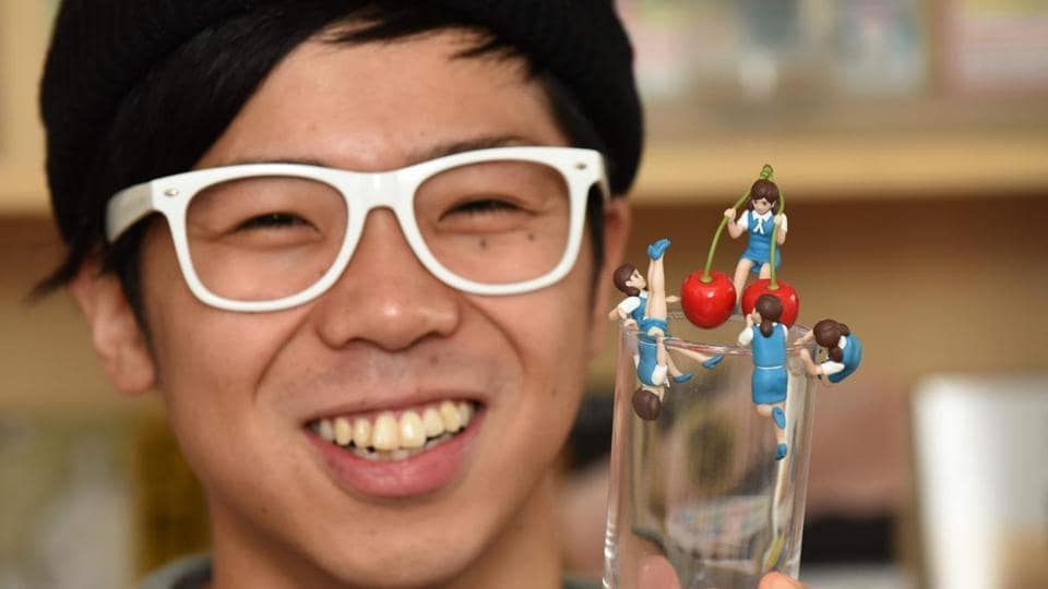 Tokyo-based manufacturer Kitan Club spokesman Seita Shiki displaying figurines of women wearing a typical office worker's clothes, whose arms or legs are designed to hang over the edge of a glass.