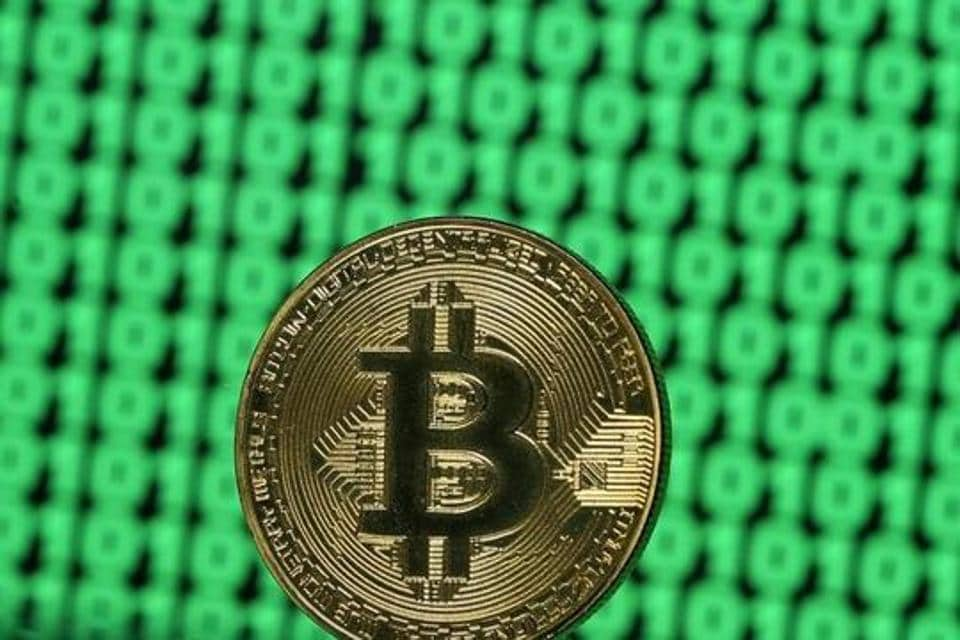 FILE PHOTO: A token of the virtual currency Bitcoin is seen placed on a monitor that displays binary digits in this illustration picture, December 8, 2017. REUTERS/Dado Ruvic/Illustration/File Photo