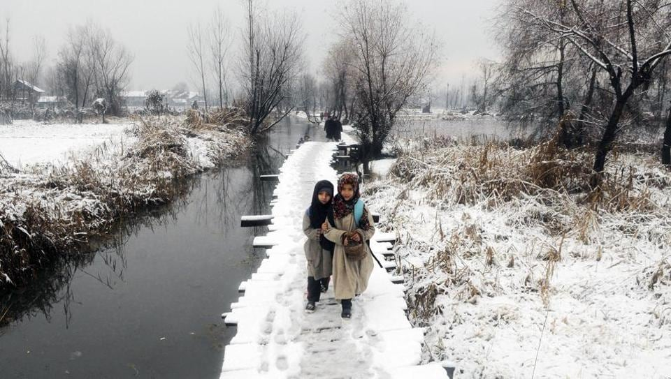 Children walk on a snow covered foot-bridge after snowfall in the interiors of Dal Lake, Srinagar. Over a month-long dry spell in Jammu and Kashmir ended Monday with the higher reaches receiving snowfall while the plains were lashed by rains, dropping temperatures at most places across Kashmir and Ladakh regions. (Waseem Andrabi / HT Photo)