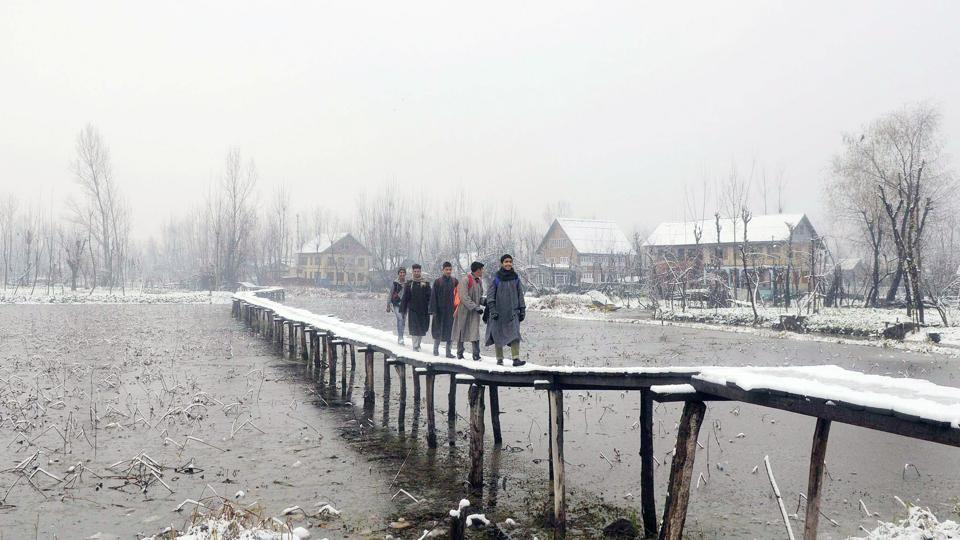 People cross the Dal through a snow covered foot-bridge in Srinagar. Snowfall in Gulmarg has brightened the prospects of winter sports at its famous ski resort. (Waseem Andrabi / HT Photo)