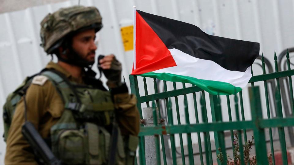 A member of the Israeli security forces stands next to a Palestinian flag during clashes with Palestinian protesters following a demonstration in the West Bank town of Hebron on December 13, 2017, as protests continue in the region amid anger over US President Donald Trump's recognition of Jerusalem as its capital.