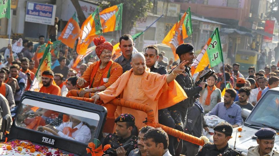 Uttar Pradesh chief minister Yogi Aditya Nath waves to the supporters of Bharatiya Janata Party during an election road show in Ahmedabad. Since an NDA government led by BJP is in power at the Centre, the UP government is hopeful that the law against organised crimes will be cleared.