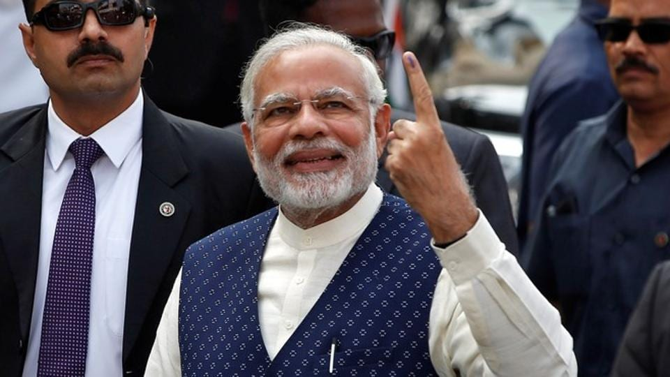 Prime Minister Narendra Modi shows his ink-marked finger after casting his vote outside a polling station during the last phase of Gujarat assembly election in Ahmedabad.