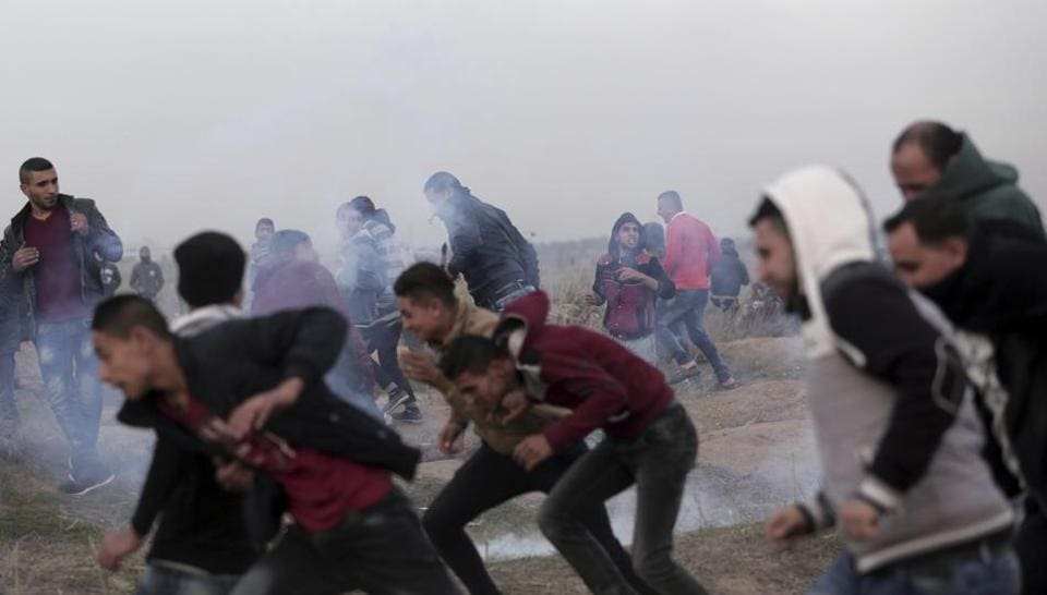 Palestinian protesters run for cover from teargas fired by Israeli troops during clashes on the Israeli border with Gaza, Sunday, Dec. 10, 2017.