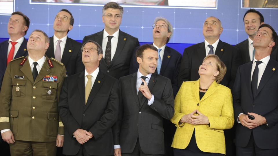French President Emmanuel Macron, front center, speaks with German Chancellor Angela Merkel, front second right, as they look up at a drone flying above their heads during a group photo at an EU summit at the Europa building in Brussels on Thursday, Dec. 14, 2017.