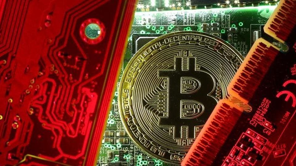A coin representing the bitcoin cryptocurrency is seen on computer circuit boards in this illustration picture.