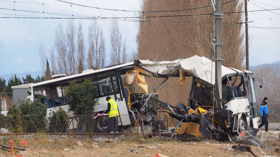 A towing service worker and a gendarme walk next to the wreckage of school bus in Millas, near Perpignan, southern France, on December 15, 2017, a day after an accident when a train crashed into the school bus at a level crossing.