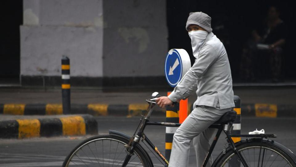 A man cycles wearing face protection amid heavy smog in New Delhi.