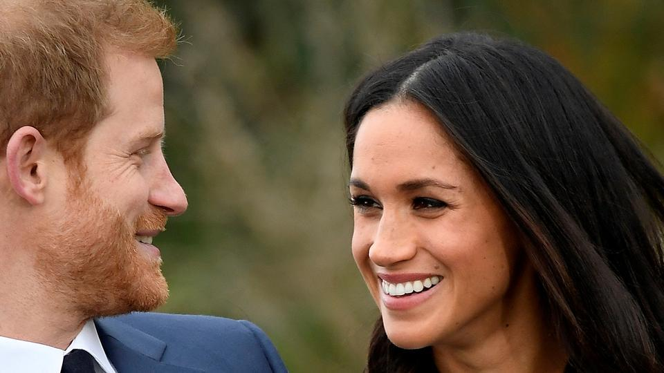 Britain's Prince Harry poses with Meghan Markle in the Sunken Garden of Kensington Palace in London on  November 27, 2017.