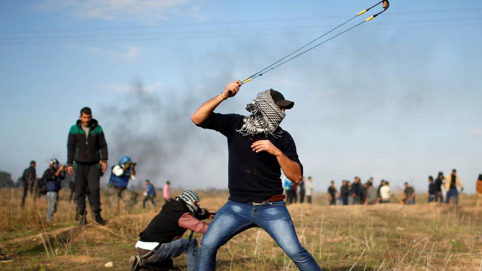 A Palestinian demonstrator uses a sling to hurl stones towards Israeli troops during clashes at a protest, near the border with Israel in the east of Gaza City.