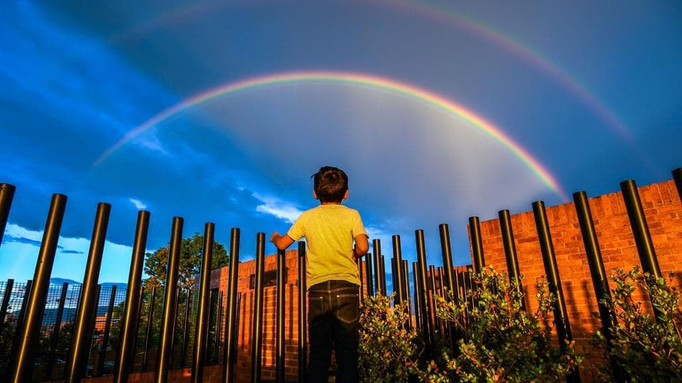 A boy looks at a rainbow during a sunset in Bogota, Spain on December 13, 2017. (Luis Acosta / AFP)