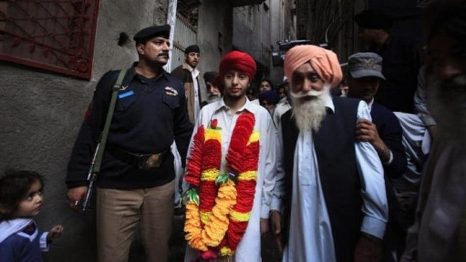 File photo of Sikhs walking through the narrow streets of Peshawar with Gorvindar Singh (centre), one of three Sikhs who was kidnapped for ransom, after his return home on March 1, 2010.