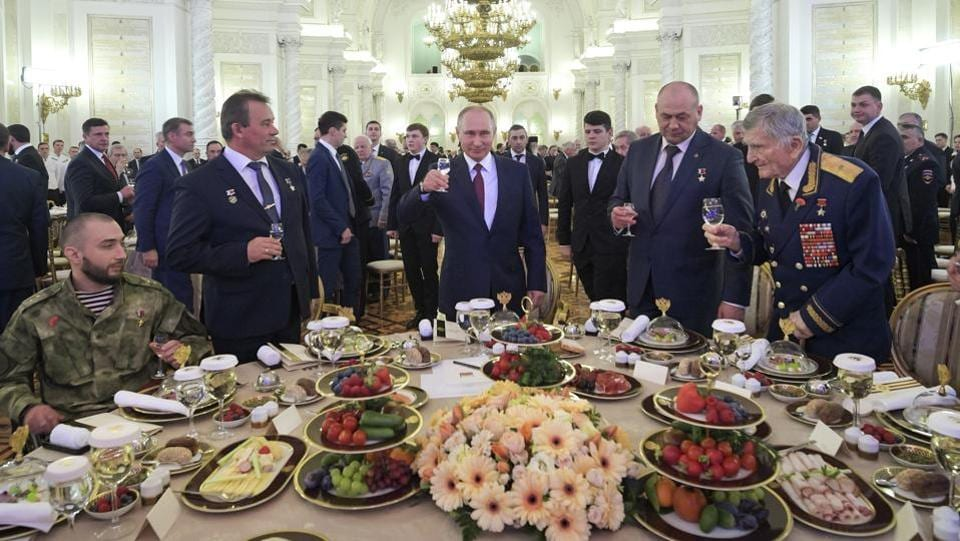 Russian President Vladimir Putin (C), make a toast as he takes part in a reception in honour of the Heroes of the Fatherland in the Kremlin in Moscow, Russia on Thursday, December 14, 2017. (Alexei Druzhinin, Sputnik, Kremlin Pool Photo via AP)