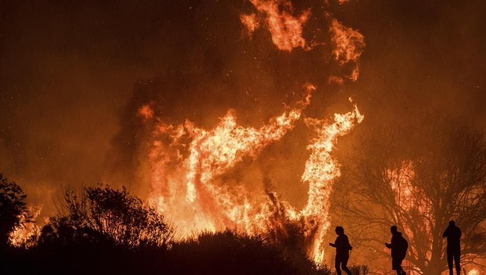 Motorists on Highway 101 watch flames from the Thomas fire leap above the roadway north of Ventura, California. Raging since December 04, wildfire Thomas became state's third largest blaze on record having already eaten through 256,000-acres (103,600-hectares). (Noah Berger / AP)