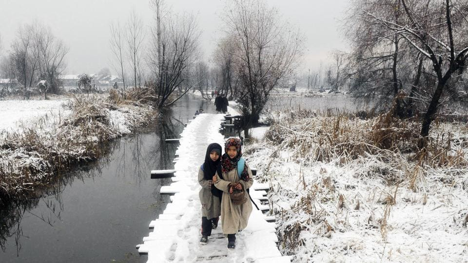 Children walk on a snow covered foot bridge after snowfall, in the interiors of Dal Lake in Srinagar on Tuesday. (Waseem Andrabi / HT Photo)