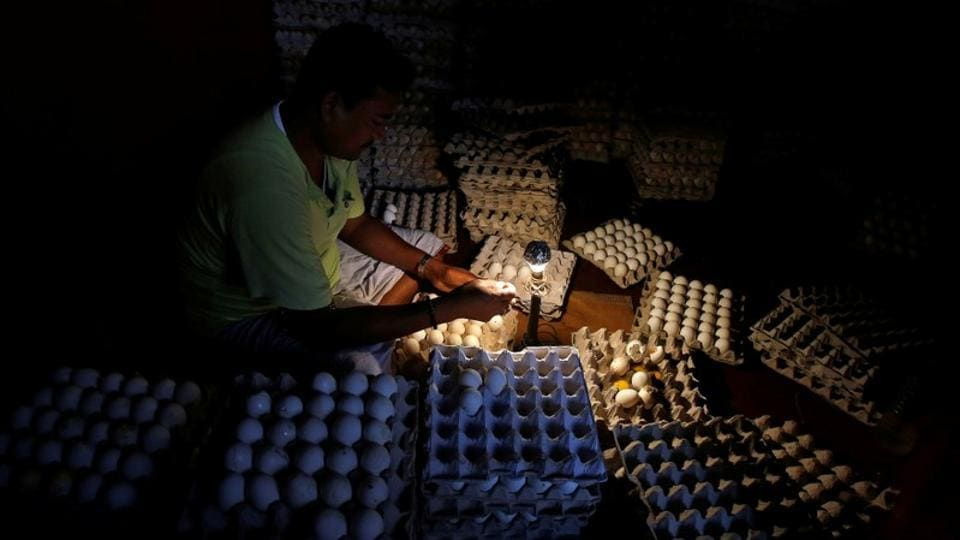 A worker checks eggs inside a wholesale egg shop at a market in Kolkata on Wednesday. (Rupak De Chowdhuri / REUTERS)