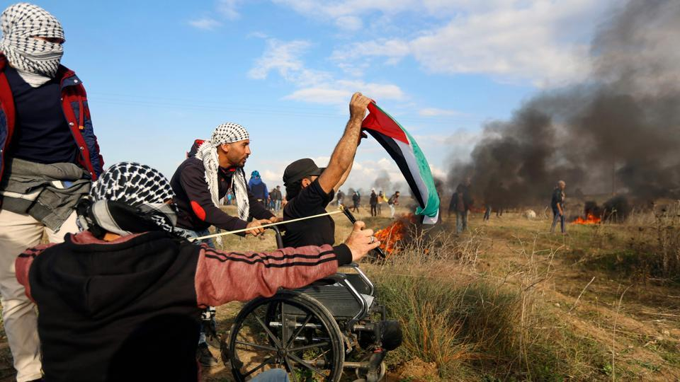 A picture taken on December 15, 2017 shows wheelchair-bound Palestinian demonstrator Ibrahim Abu Thurayeh waving a Palestinian flag amidst smoke from flaming tires during a protest along the Gaza-Israel border, as clashes during clashes with Israeli security forces against Washington's recognition of Jerusalem as Israel's capital intensified.