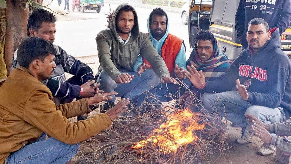 Men sit around a bonfire to protect themselves from the cold at Airport Road in Mohali.  (Sushil Prajapati/HT)