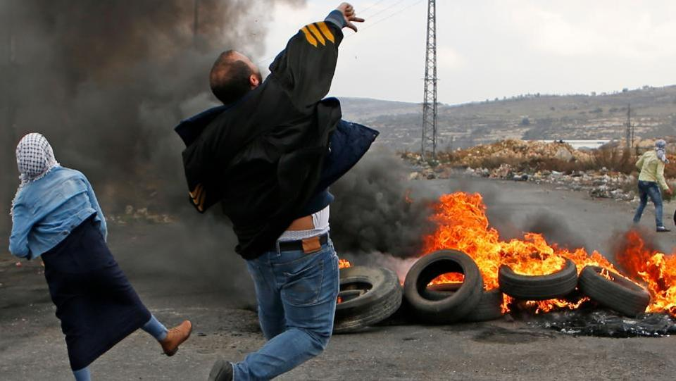 Palestinian protestors throw stones towards Israeli security forces during clashes following a demonstration in the West Bank city of Ramallah on December 13, 2017, as protests continued in the region over US President Donald Trump's recognition of Jerusalem as Israel's capital. (Abbas Momani / AFP)