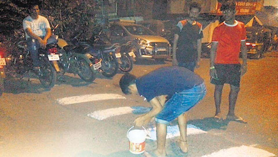Youngsters paint stripes on speed breakers in Kurla on Saturday.