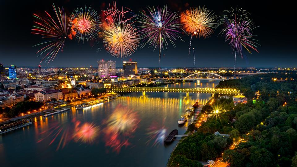 Fireworks over Danube river with evening lights in the capital city of Bratislava.