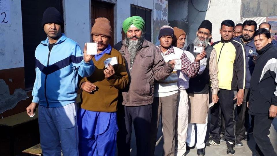 People waiting outside a polling booth in Jalandhar on Sunday.