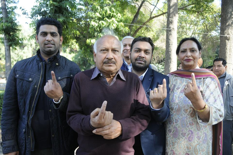 Health minister Brahm Mohindra with his family showing ink mark after casting his vote in Patiala . (Bharat Bhushan/HT)