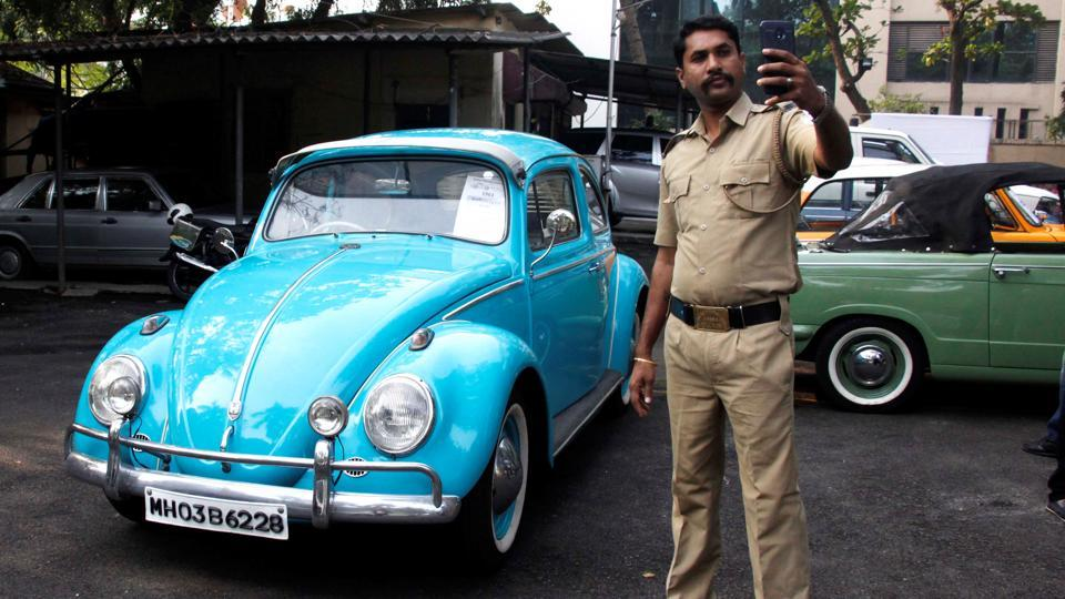 A policeman takes a selfie with a vintage car at the event. (Hemanshi Kamani /HT Photo)