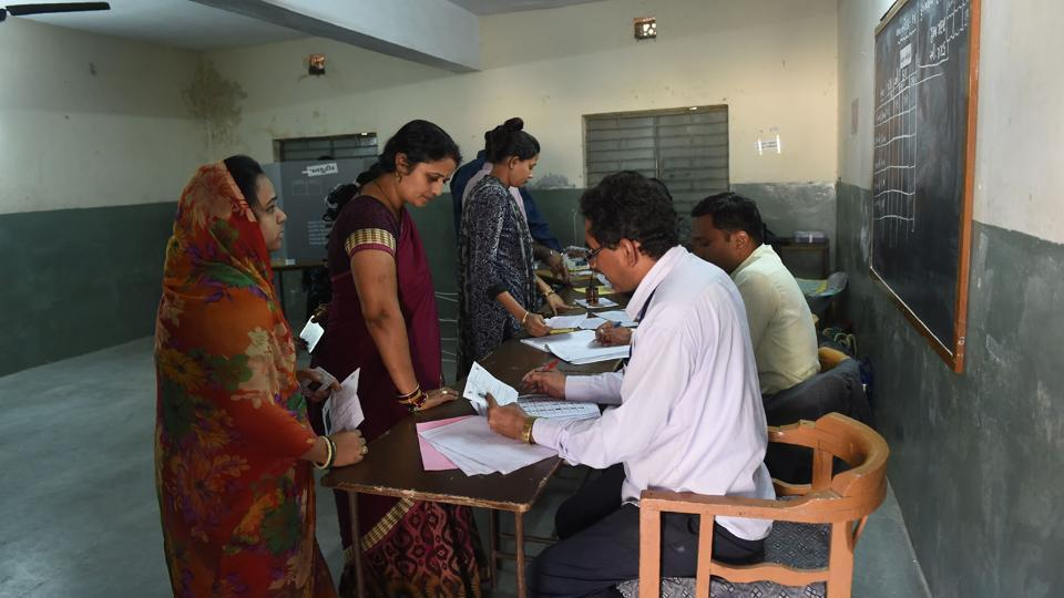 Polling officials verify electoral documents of voters in a re-polling centre at Nava Naroda on the outskirts of Ahmedabad on December 17.