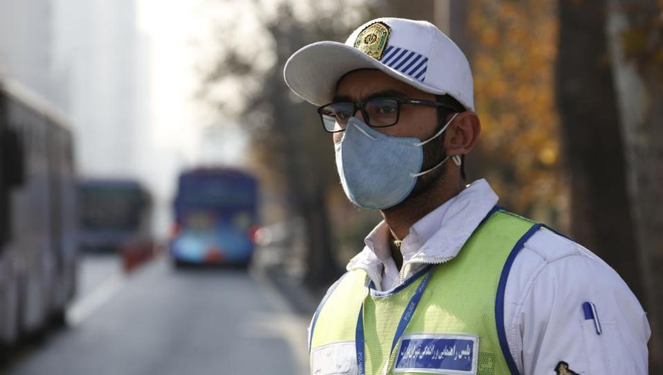 An Iranian traffic officer wears a face mask in Tehran as winter's heavy pollution has hit new highs in the capital, on December 17, 2017.