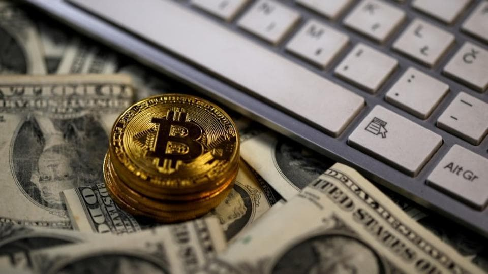 Bitcoin (virtual currency) coins placed on Dollar banknotes, next to computer keyboard, are seen in this illustration picture, November 6, 2017.