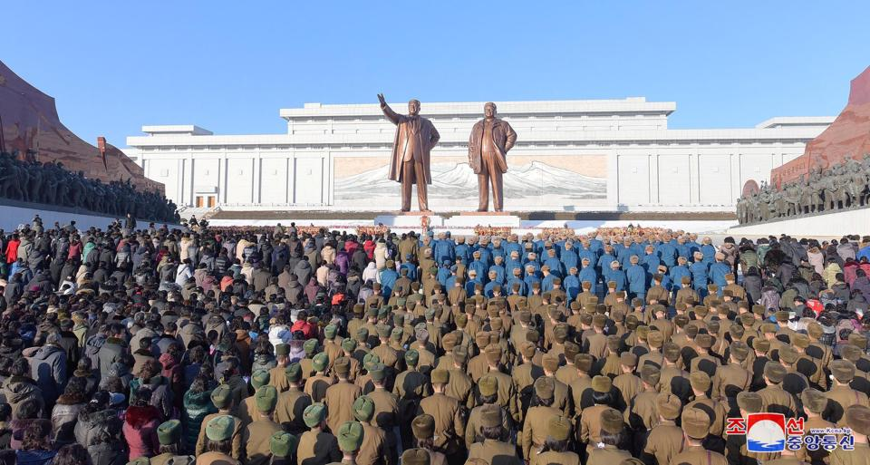 North Korean servicepersons and civilians visit the statues of former leaders Kim Il Sung and Kim Jong Il in Pyongyang on December 17, 2017.