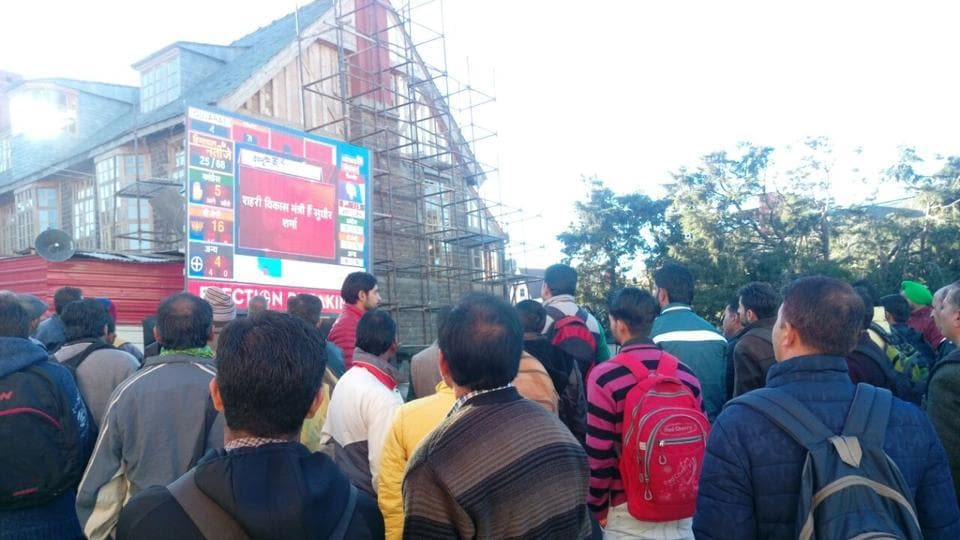 People watching live updates of HP assembly results at Scandal Point on Mall road in Shimla on Monday. (Deepak Sansta/HT)