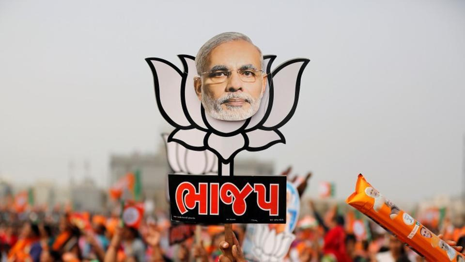 A supporter holds up a cut-out of a lotus, the election symbol of India's ruling BJP, with an image of Prime Minister Narendra Modi in Ahmedabad.