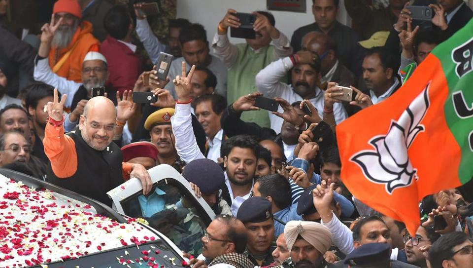 BJP president Amit Shah flashes the victory sign as he is welcomed at the party headquarters in New Delhi on Monday. The party won the assembly elections in both Gujarat and Himachal Pradesh.